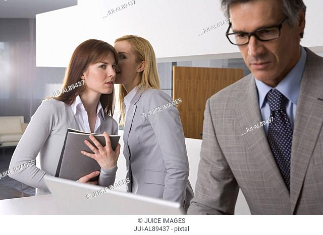 Two businesswomen telling secret