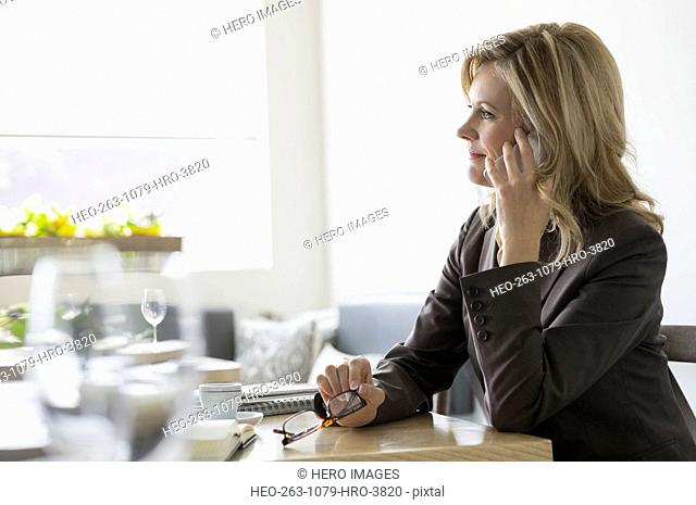 Businesswoman talking on cell phone at bistro table