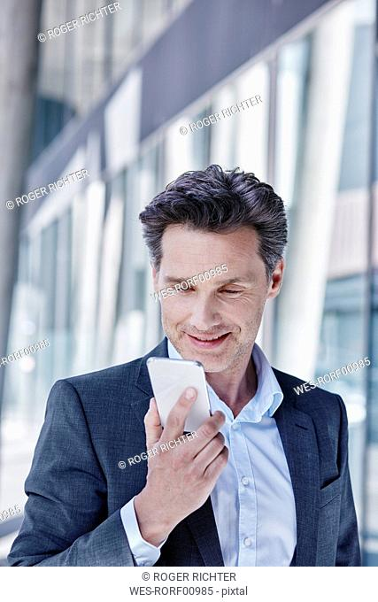 Portrait of smiling businessman using cell phone