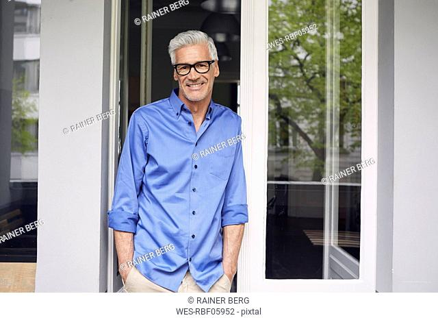 Portrait of smiling mature man leaning against balcony door