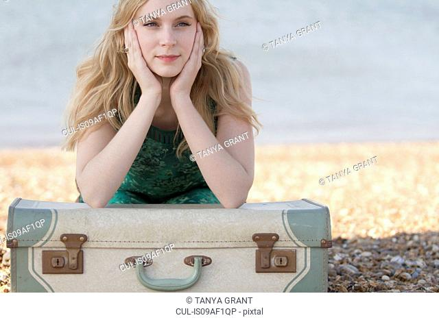 Portrait of young woman with suitcase on beach, Whitstable, Kent, UK