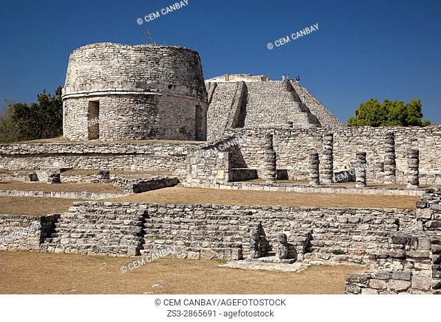 View to the Templo Redondo-Round Temple and to the visitors climbing up to the Castle of Kukulcan-Castillo de Kukulcan in the background in Mayapan...
