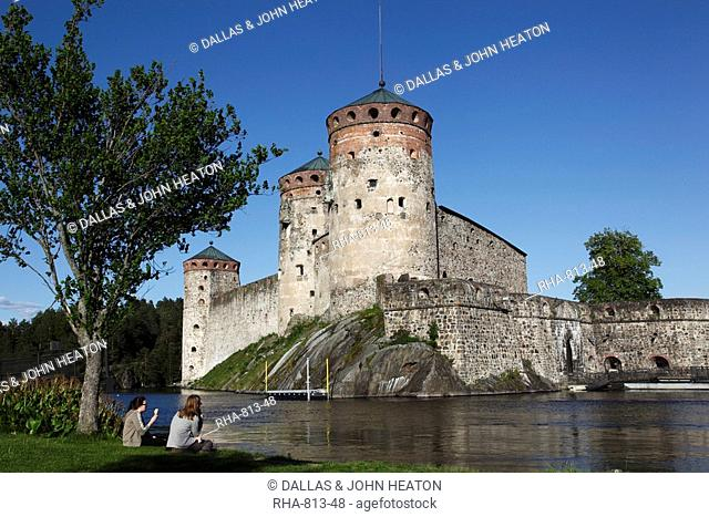 Girls relaxing beside Olavinlinna Medieval Castle St. Olaf's Castle, Savonlinna, Saimaa Lake District, Savonia, Finland, Scandinavia, Europe