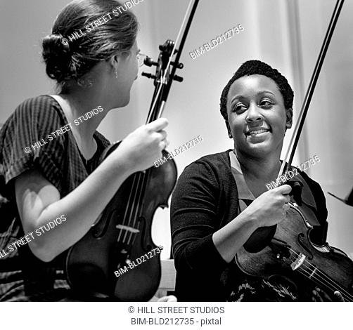 Students playing violin in college orchestra