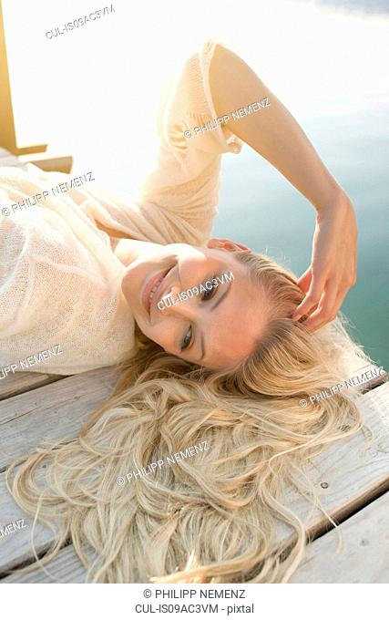 Young woman lying on lake pier