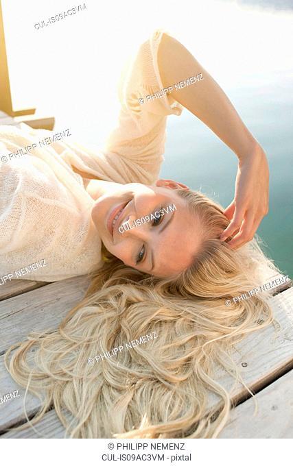 Young woman lying on lake pier