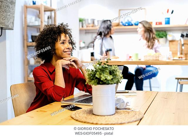 Smiling woman with laptop sitting at table
