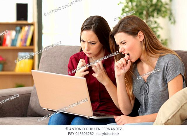 Two angry friends watching media on line with a pc sitting on a sofa in the living room at home