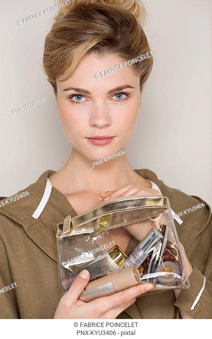 Beautiful woman holding a make-up bag