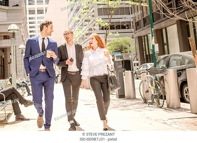 Young businesswoman and businessmen with takeaway coffee strolling along sidewalk, New York, USA
