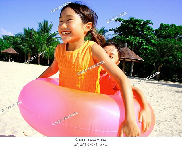 Two girls playing on the beach with an inner tube