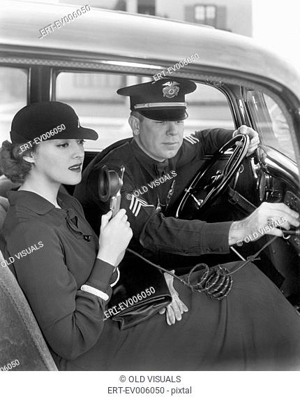 Woman sitting next to a policeman in his car holding a microphone in her hand All persons depicted are not longer living and no estate exists Supplier...