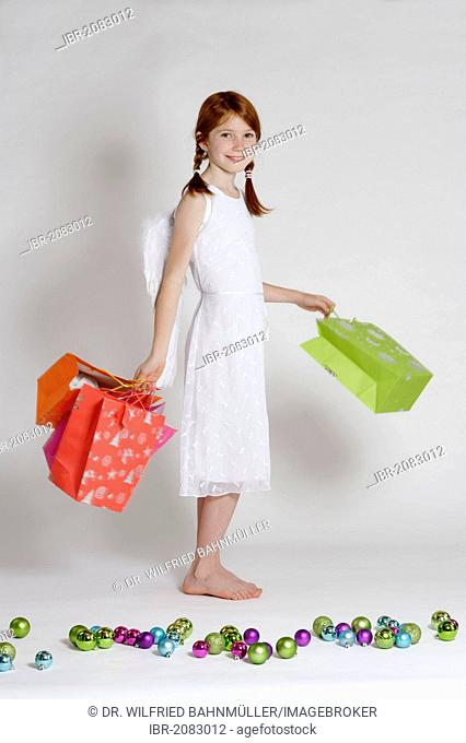 Girl dressed up as Christmas angel, Christ Child with presents