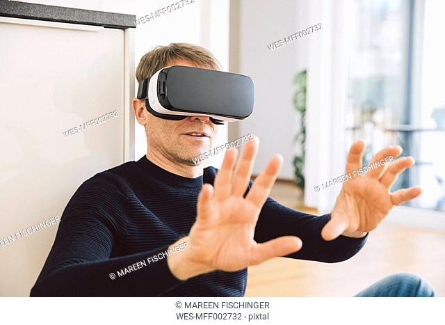 Man wearing virtual reality glasses using his hands