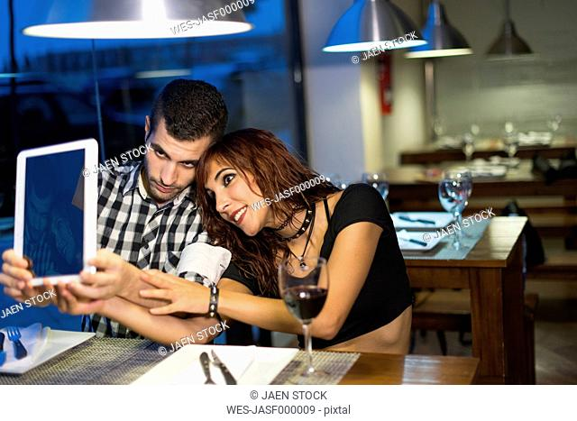 Young couple in modern restaurant taking a selfie with digital tablet