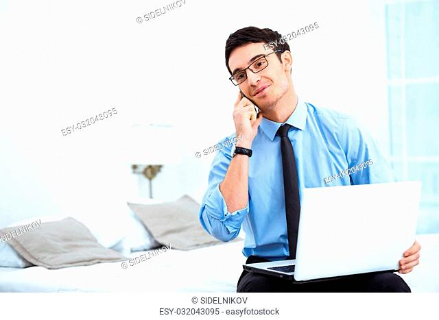 Young smiling businessman using phone and laptop while sitting in cozy hotel room