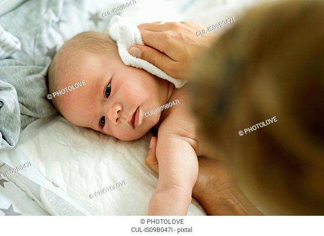 Mothers hand washing baby sons face