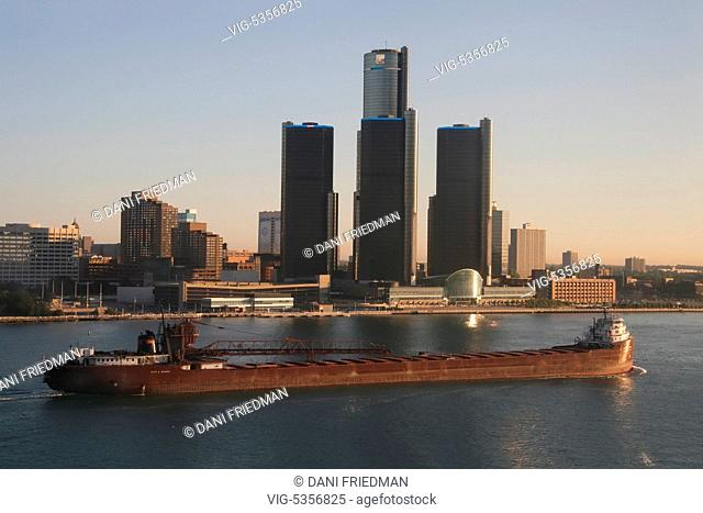 A large bulk carrier cargo ship travels along the Detroit River and passes the GM Renaissance Centre along the skyline of downtown Detroit, Michigan, USA