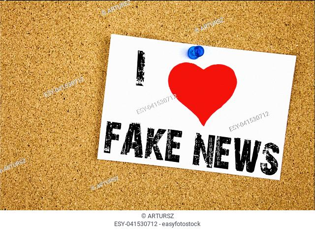 Hand writing text caption inspiration showing I Love Fake News concept meaning Propaganda Newspaper Fake News Loving written on sticky note