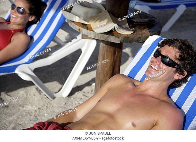 Young couple sunbathing on beach, Mayan Riviera,Yucatan Peninsular,Quintana Roo State,Mexico