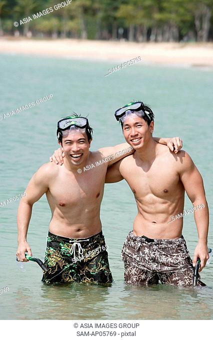 Two men standing in sea, arms around each other