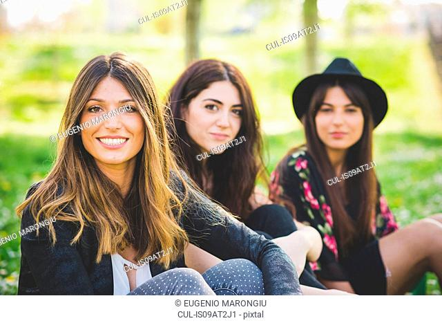 Portrait of three young female friends sitting in park