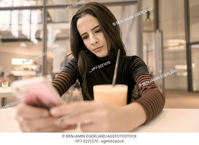 portrait of emotional woman using phone while taking a break with juice glass at table in café, in Munich, Germany