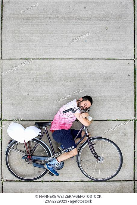 Boy spooning with his bicycle on the pavement