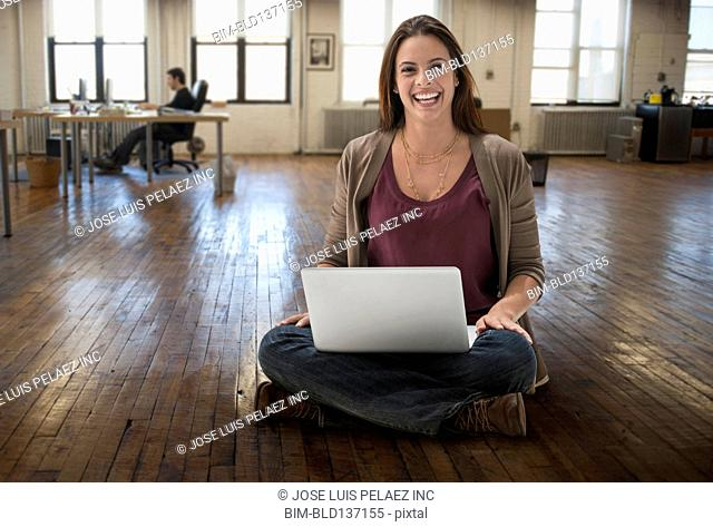 Caucasian businesswoman using laptop on office floor