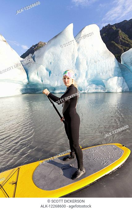 One woman stand up paddleboarding in front of Grewingk Glacier, Kachemak Bay State Park, Southcentral Alaska