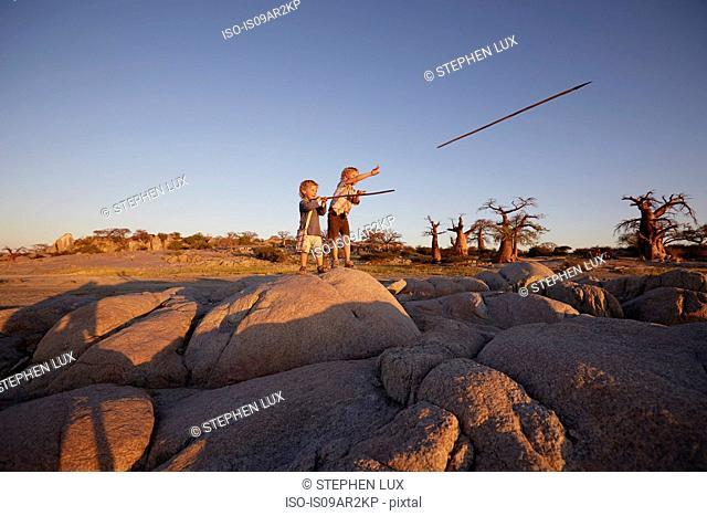 Two young boys standing on rock, throwing spears, Gweta, makgadikgadi, Botswana