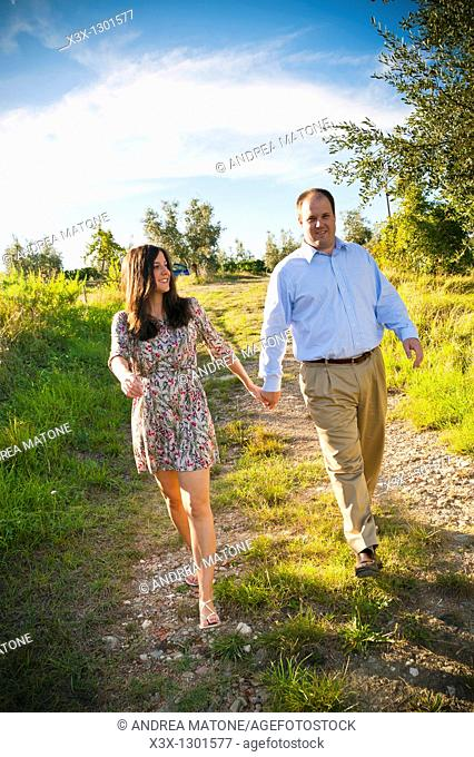 Couple walking hand in hand in a field Tuscany Italy