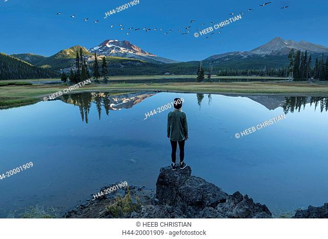 Oregon, Deschutes County, Bend, Sparks Lake, woman at lake with geese flying, MR, (m)