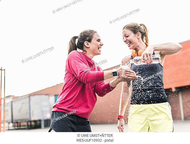 Two playful women with water bottle having a break from exercising