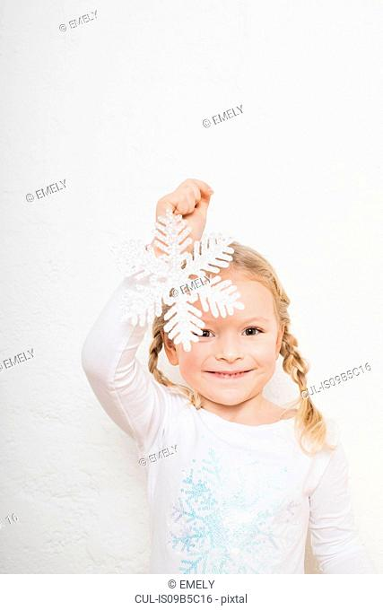 Portrait of young girl against white background, holding snowflake