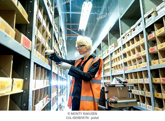 Female apprentice picking parts in car factory
