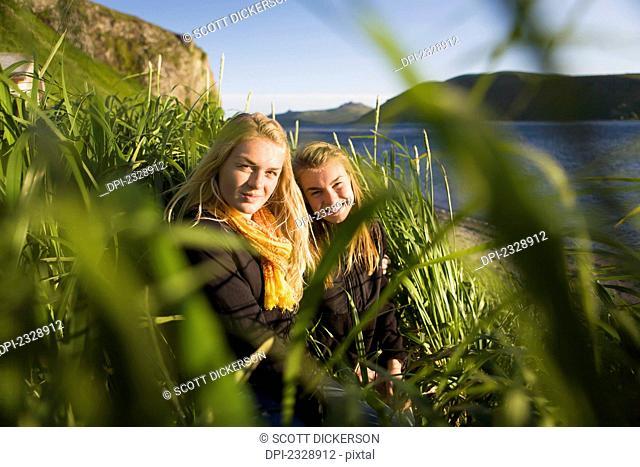 Two Sisters Enjoying The Sunshine At The Water's Edge; False Pass, Alaska, United States Of America