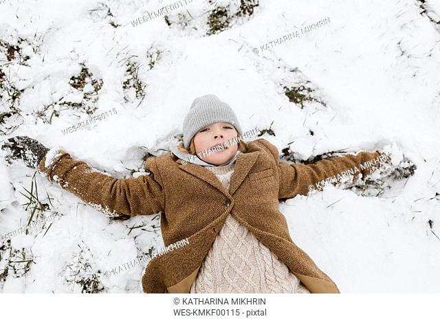 Portrait of boy lying on snow-covered meadow making a snow angel