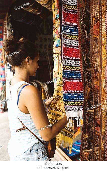 Young woman shopping for textiles at market stall, Lake Atitlan, Guatemala