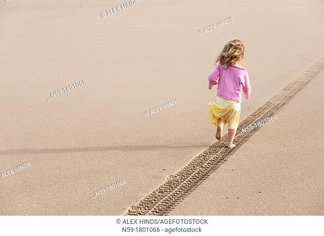 Young girl, four years old, running along a tyre track on a sandy beach