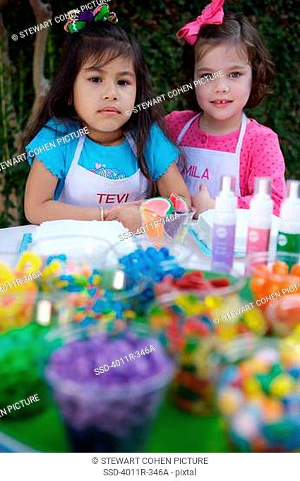 Two girls decorating birthday cakes