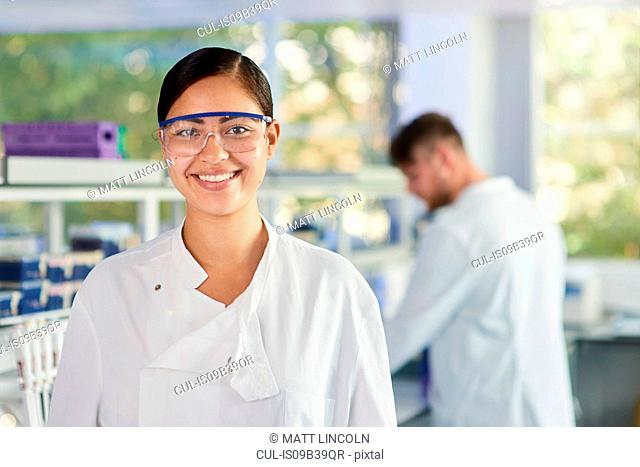 Scientist wearing safety glasses smiling at camera