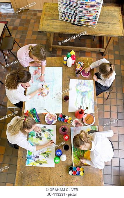 Art teacher guiding middle school students painting in art class