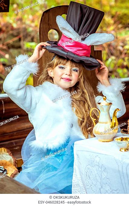 An little beautiful girl in the scenery of Alice in Wonderland holding cylinder hat with ears like a rabbit over head at the table in the garden