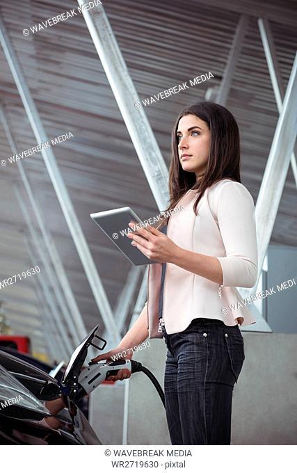 Beautiful woman using digital tablet while charging electric car