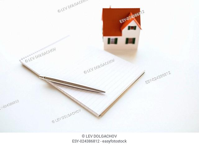 building, mortgage, real estate and property concept - close up of house model, notebook and pencil