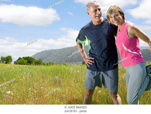 Active couple stretching before exercising in remote area
