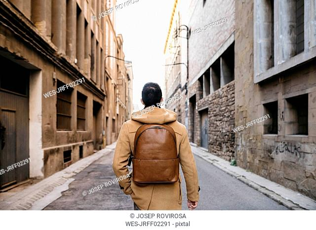Spain, Igualada, rear view of man with backpack walking through the industrial zone of the town