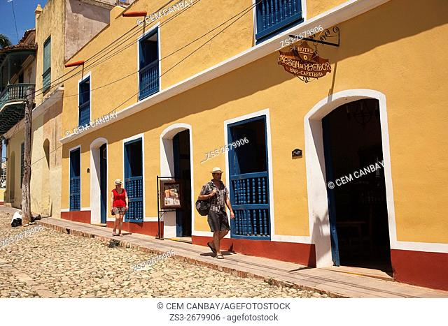 Tourists walking at the cobblestone streets of the town, Trinidad, Sancti Spiritu Province, Cuba, West Indies, Central America