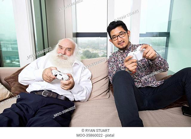 Portrait of grandson playing video game on sofa at home